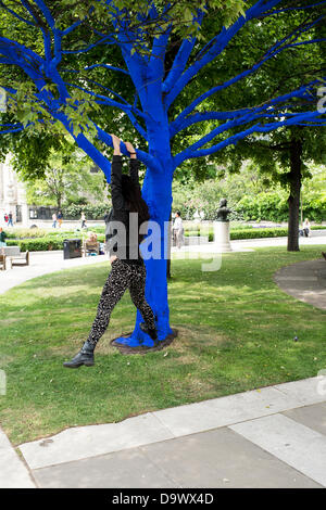 London, UK. 27th June 2013. Festival Gardens, City of London. People interact with one of the trees painted blue - Stock Photo