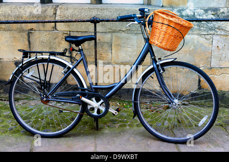 A blue ladies' bike with a front wicker basket on the handlebars, leaning against railings outside outdoor outdoors - Stock Photo