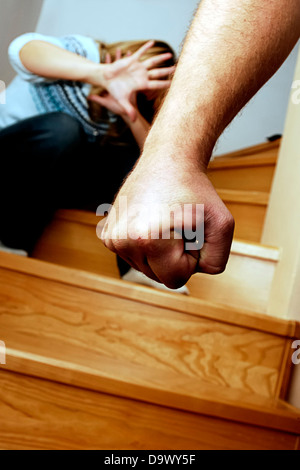 menacing male hand with an afraid woman crouched in the background - domestic violence concept - Stock Photo