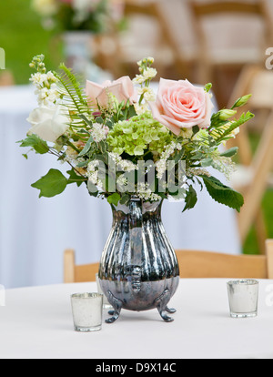 flower arrangement in old silver pitcher - Stock Photo