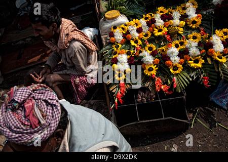 Flower seller flowers stall in Mullick ghat flower market. Calcutta,West Bengal, India - Stock Photo