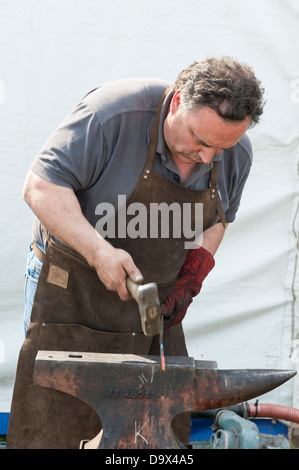 A blacksmith hammering red hot metal on an anvil during a competition at the Royal Cornwall Show 2013 - Stock Photo
