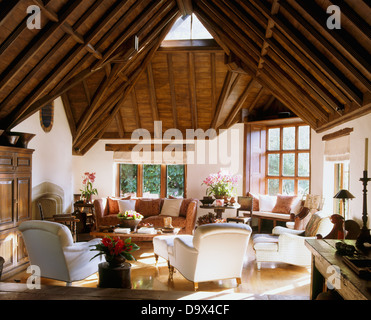 High, vaulted beamed roof in large barn conversion sitting room with white armchairs and sofa and peach Knole sofa - Stock Photo