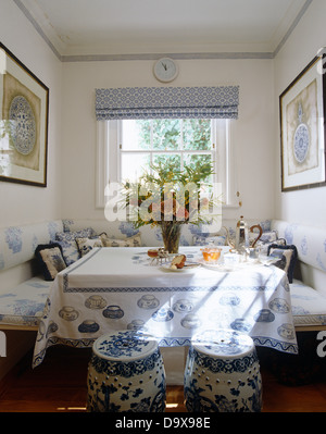 Blue+white Chinese pottery stools at table with teacup themed cloth and bench seating with blue+white cushions - Stock Photo
