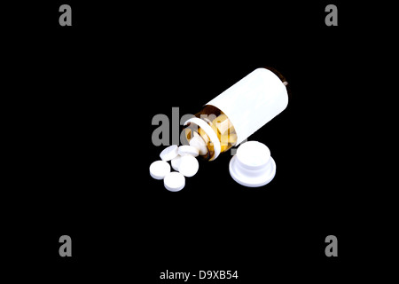 Suplements pills on the table with dose isolated on a black background - Stock Photo