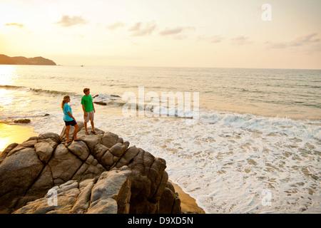 Couple with dog hiking on beach rocks - Stock Photo