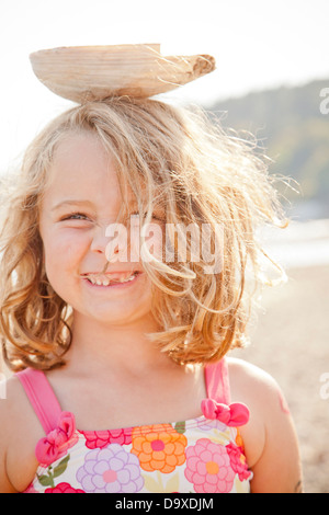 Young girl balancing large seashell on her head - Stock Photo