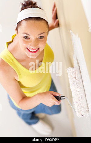overhead view of young woman painting the wall - Stock Photo