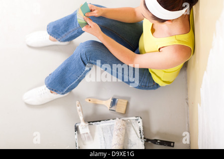 overhead view of young woman choosing paint color - Stock Photo