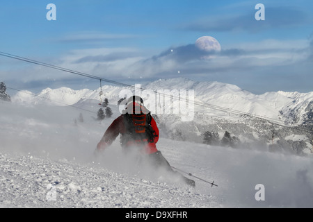 Skier is carving on a slope with daylight moon on horizon - Stock Photo