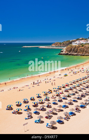 Holidaymakers sunbathing under beach umbrellas on the sandy beach Praia do Túnel Albufeira Beach Algarve Portugal - Stock Photo