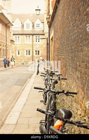 A row of bikes parked against a brick wall in Cambridge. - Stock Photo