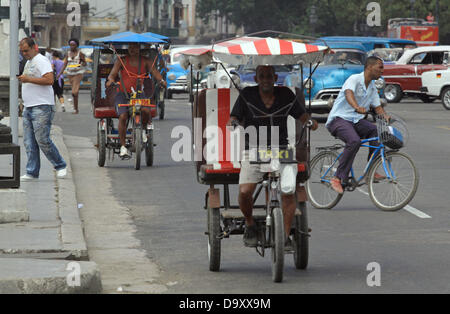 Bike taxis and vintage cars from the 1960s are pictured opposite the Capitolio in the city center of Havana, Cuba, - Stock Photo