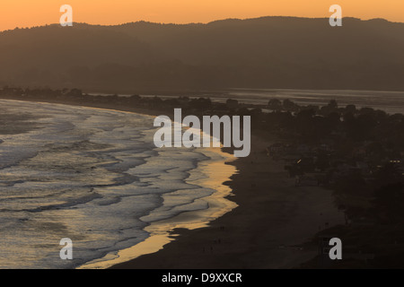 Sunset glows over the mountains onto curving beach water's edge at Bolinas Bay on Stinson Beach near San Francisco - Stock Photo