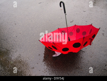 Rainy day photograph with red and black umbrella - Stock Photo