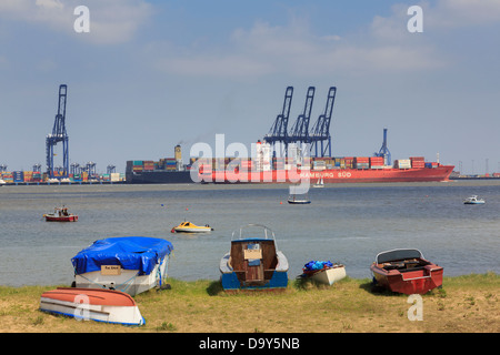 Small boats on seashore with a container ship docked in Felixstowe port across river Orwell estuary. Harwich Essex - Stock Photo