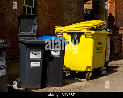 Black wheelie bins and yellow plastic skip used to collect domestic and commercial waste in a street in Wirksworth - Stock Photo