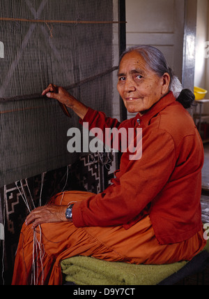 USA New Mexico Senior woman weaving Two Grey Hills Navajo Rug from her Churro Sheep wool on loom in her home near - Stock Photo