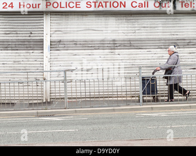 A woman walking past a row of closed down shops in Stretford, Manchester, England, UK - Stock Photo