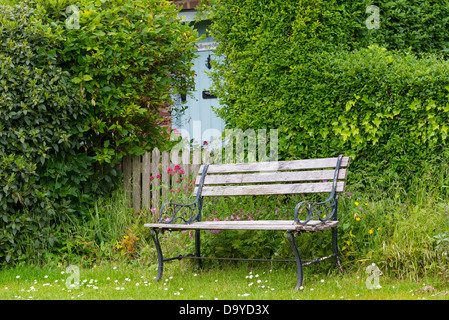 Country cottage view with garden seat, garden gate and front door, Norfolk, England. - Stock Photo