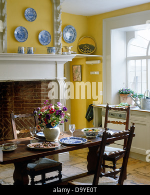 ladderback chairs at antique oak table set for lunch in yellow country dining room - Oak Table And Chairs
