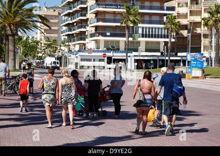 british and spanish holidaymakers walk along tree lined seafront promenade salou catalonia spain - Stock Photo