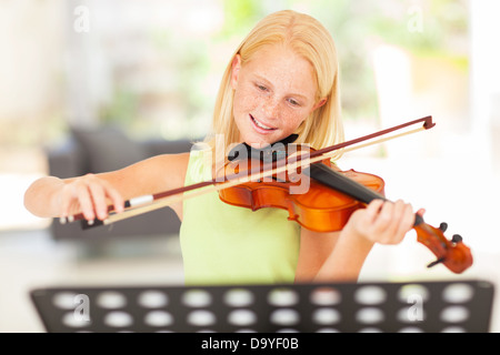 pretty preteen girl practicing violin at home - Stock Photo