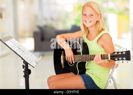 cheerful preteen girl practicing guitar at home - Stock Photo