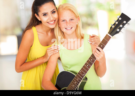 happy preteen girl with her music teacher - Stock Photo