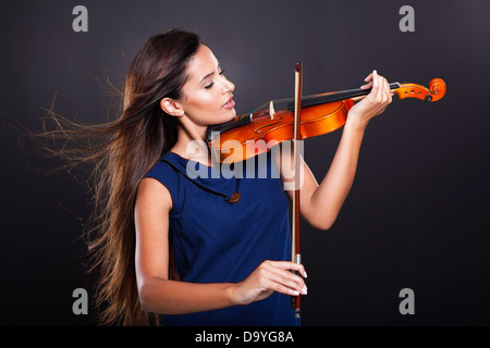 beautiful young woman playing violin on black background - Stock Photo