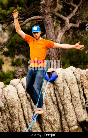 A male highliner walks the Elephant Buttresses highline in Boulder Canyon, Colorado. - Stock Photo