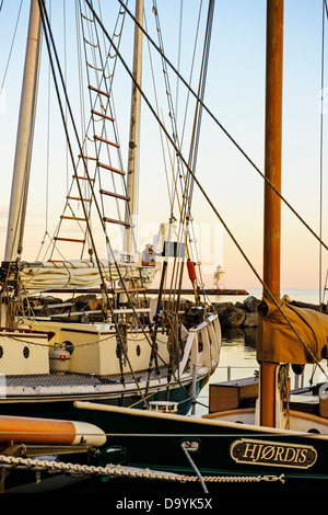 Sailboats at dock in Grand Marais Harbor with breakwater lighthouse in background. - Stock Photo