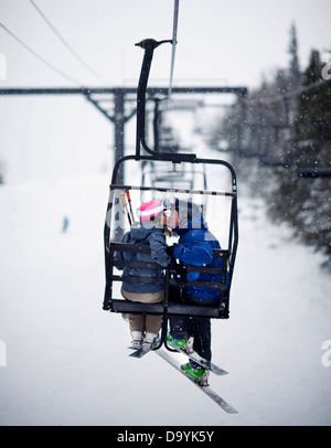 A couple share a kiss on a chairlift in softly falling snow. - Stock Photo