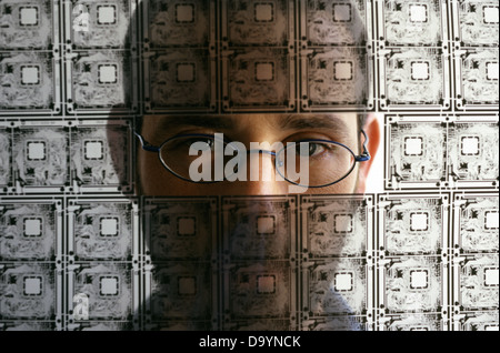 An Israeli technician looking through transparent electric circuit board in a high tech company Israel - Stock Photo
