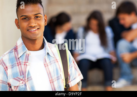 handsome Indian teenage high school student carrying schoolbag - Stock Photo