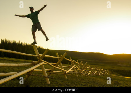 A man balancing on a fence at sunset, Rio Grande National Forest, Creede, Colorado(silhouette). - Stock Photo