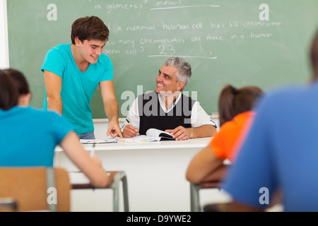 friendly senior high school teacher helping a student with the class work - Stock Photo