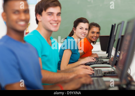 group of cheerful high school students using computers at school - Stock Photo