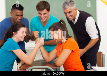 cheerful female high school students playing arm wrestling in classroom - Stock Photo