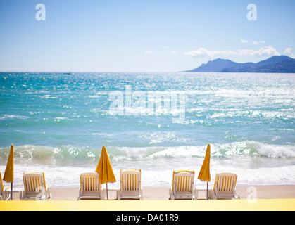 Row of yellow umbrellas and beach chairs on Mediterranean. - Stock Photo