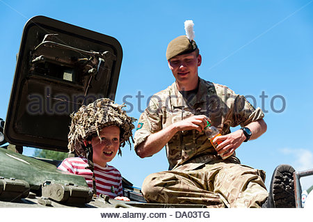 Cardiff, Wales, UK. 29th June 2013. Armed Forces Day 2013 Cardiff, UK. Young boy trying an armoured vehicle belonging - Stock Photo