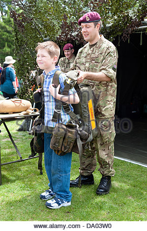 Cardiff, Wales, UK. 29th June 2013. Armed Forces Day 2013 Cardiff, UK. Young boy trying on army equipment. Credit: - Stock Photo