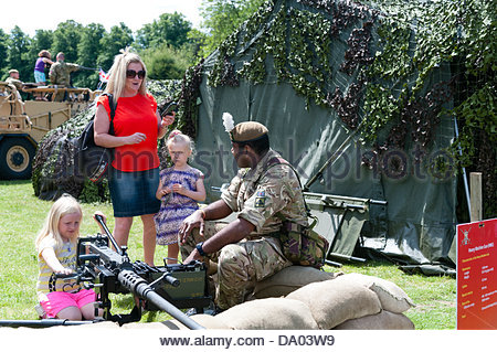 Cardiff, Wales, UK. 29th June 2013. Armed Forces Day 2013 Cardiff, UK. Young girl trying a heavy machine gun supervised - Stock Photo