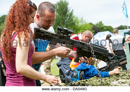 Cardiff, Wales, UK. 29th June 2013. Armed Forces Day 2013 Cardiff, UK. Man showing a woman an army rifle. Credit: - Stock Photo