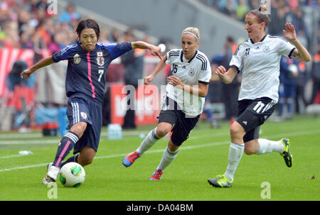 Germany's Anja Mittag (R-L) and Jennifer Cramer vie for the ball with Japan's Kozue Ando during the Women's international - Stock Photo