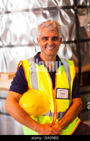 portrait of senior shipping company worker holding his helmet in warehouse - Stock Photo