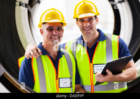 cheerful shipping company inspectors standing in between huge industrial tires - Stock Photo