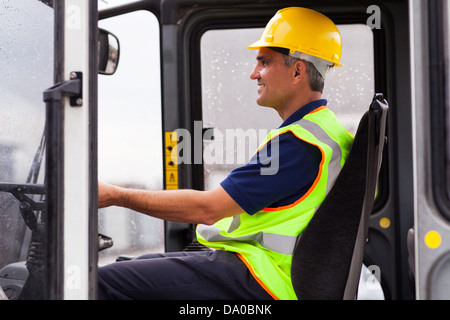 middle aged professional warehouse worker operating forklift - Stock Photo