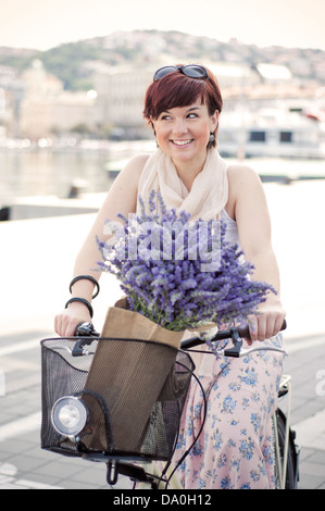 Women riding a retro bike with lavender flowers in basket - Stock Photo