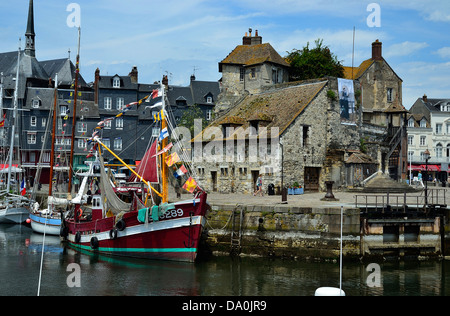Old fishing boat in the old port (Vieux Bassin), in front of The Lieutenance (medieval building). Normandy, Calvados, - Stock Photo